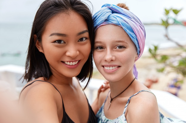 Outdoor shot of happy female tourists have stroll near sea, breath fresh marine breeze, make selfie, have positive smiles on faces. european female with scarf on head meets with her asian friend