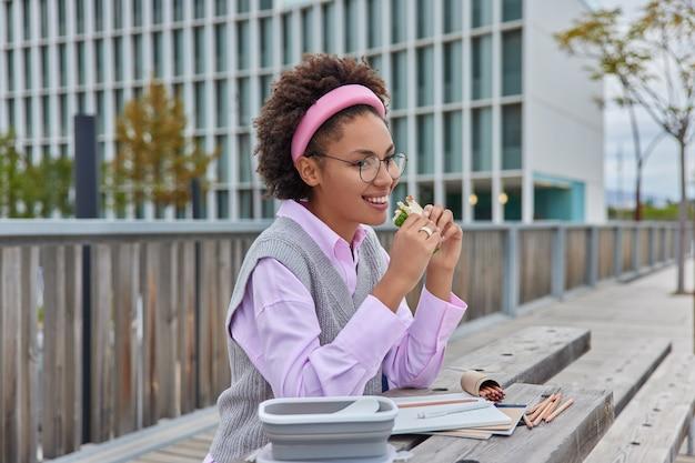 Colpo all'aperto di una donna felice che mangia un delizioso panino disegna su un quaderno con pastelli lavora su un progetto creativo crea immagini indossa occhiali trasparenti camicia elegante e gilet posa contro l'area urbana