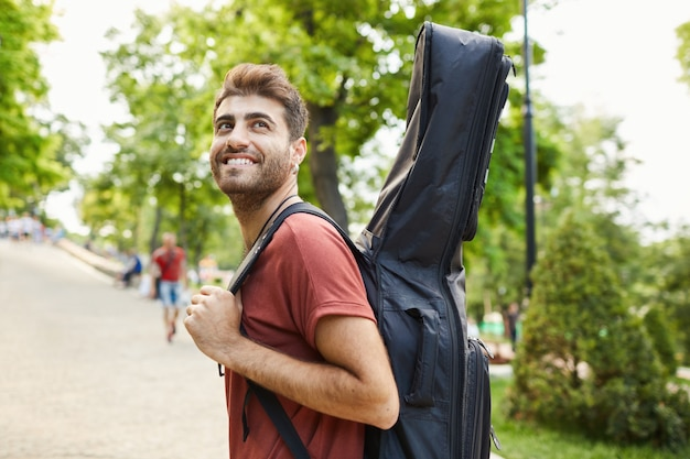Outdoor shot of happy handsome hipster guy admire beautiful green park, walking with guitar, musician going on rehearsal