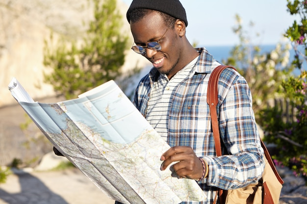 Outdoor shot of happy smiling young attractive african tourist in picturesque landscape reading paper map, searching for route and new sightseeing, wearing fashionable round mirrored lens shades