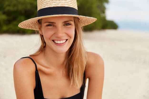 Outdoor shot of happy young woman with long hair, sunbathes on tropical beach, wears straw hat, being satisifed after swimming or walking on coastline. leisure in summer and happiness concept