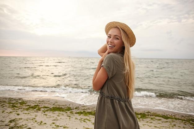 Colpo all'aperto di gioiosa giovane attraente donna bionda dai capelli lunghi mantenendo il suo cappello con la mano alzata e ridendo allegramente mentre guarda allegramente sopra la sua spalla