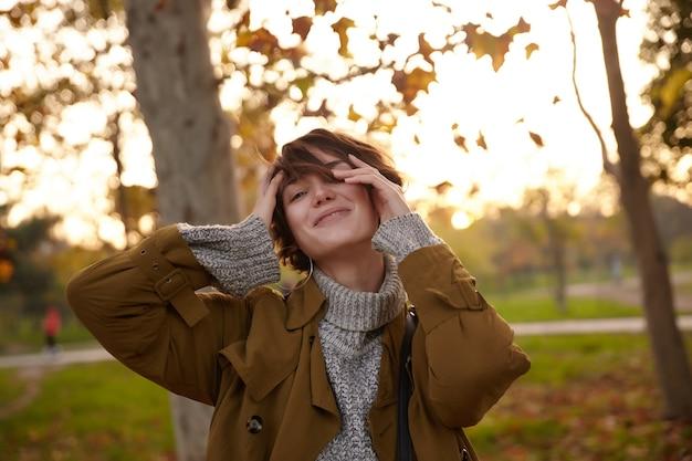 Colpo all'aperto di bella giovane donna dai capelli castani con taglio di capelli corto che tocca il viso con le mani alzate e guarda positivamente, camminando sul giardino della città dopo il lavoro