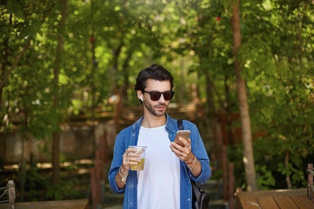 Outdoor shot of lovely young dark haired man in blue shirt and sunglasses walking along green park alley, checking mails with his smartphone while drinking lemonade