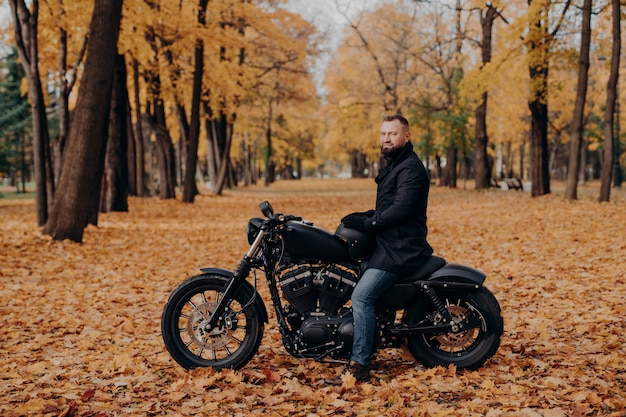 Outdoor shot of male biker with thick beard, wears protective gloves