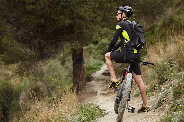 Outdoor shot of male cyclist wearing cycling clothing and protective gear standing on path in forest with his black electric bike and looking around, searching for best best trail for mountain biking