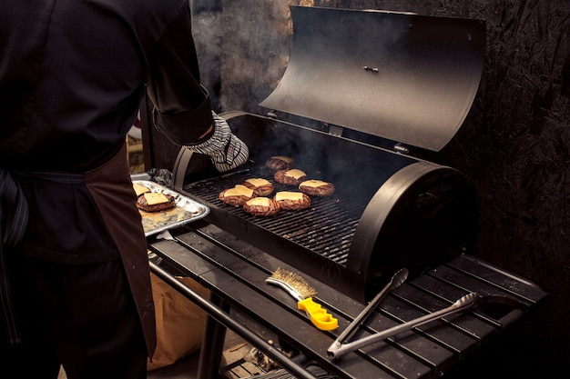Outdoor shot of man cooking meat for cheeseburger on grill