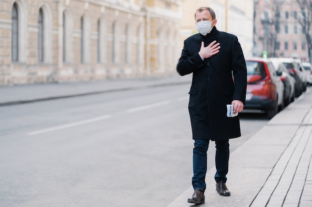 Outdoor shot of man goes to work, has problems with breathing, keeps hand on breast, wears medical mask, concerned with pandemic disease, poses outdoor. viruses attack, health problem concept