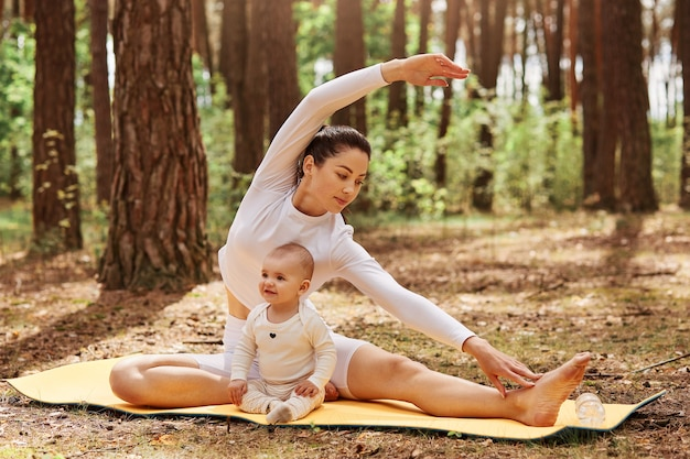 Outdoor shot of mother and infant baby posing on karemat in forest