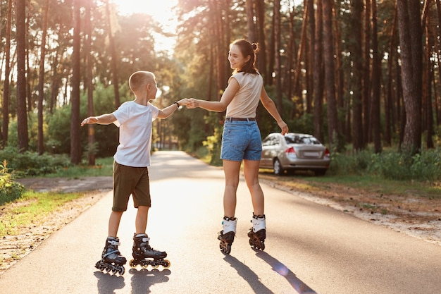 Outdoor shot of mother and son on roller skates having together, woman with her child dancing while rollerblading in summer park, happy family spending tome in nature in actively.