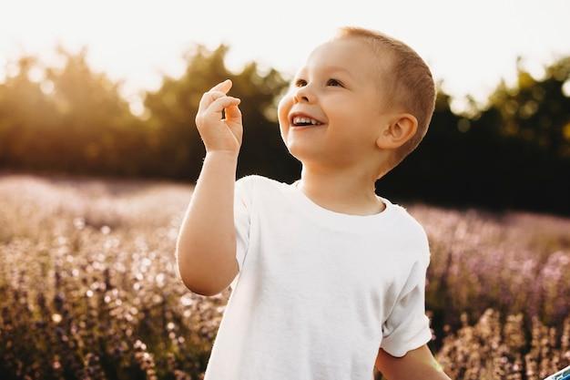 Открытый выстрел сладкий ребенок улыбается против заката. закройте прекрасный маленький мальчик, весело в поле цветов.