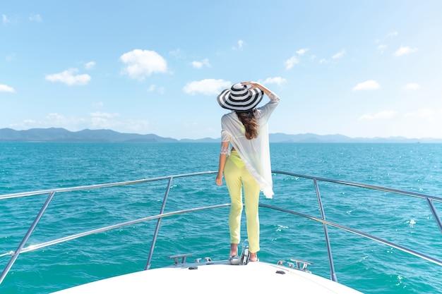 Снимок очаровательной молодой женщины в летнем костюме и шляпе, стоящей на краю яхты на открытом воздухе