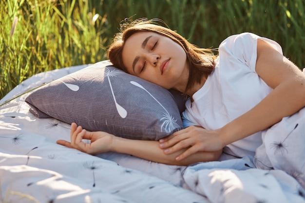 부드러운 침대에 누워 흰색 티셔츠를 입고 매력적인 검은 머리 여자의 야외 촬영