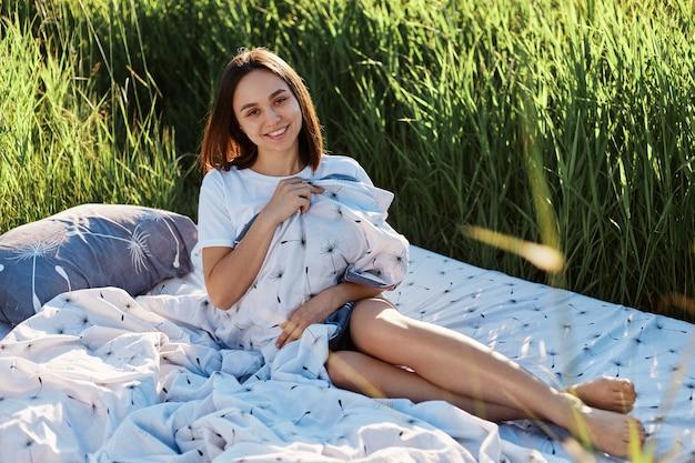 필드 한가운데에 침대에 앉아 담요를 껴안은 매력적인 여성의 야외 촬영, 카메라에 직접 웃고 행복과 긍정적 인 감정을 표현합니다.