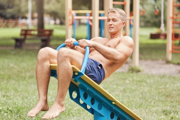 魅力的なフィットの健康な若い男性の屋外撮影は、特別なスポーツ機器で腹筋を動作します