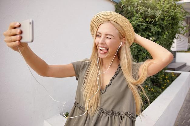 スマートホーンで自分撮りをし、ウィンクして舌を見せ、カジュアルなリネンのドレスと麦わら帽子を身に着けている魅力的な若い女性の屋外ショット