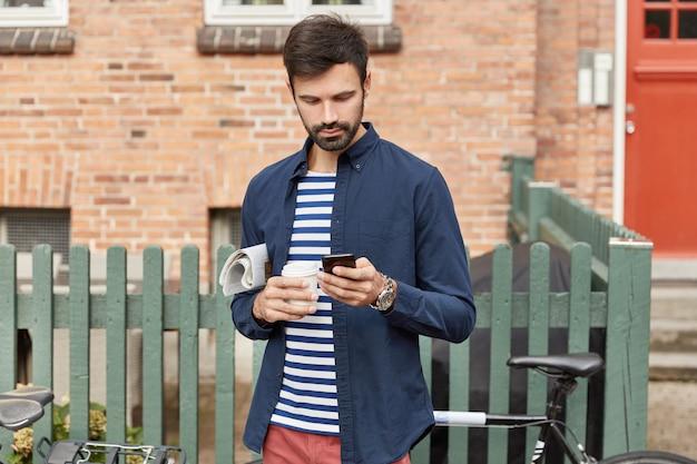 Снимок на открытом воздухе: бородатый сконцентрированный мужчина использует смартфон, несет газету и чашку кофе