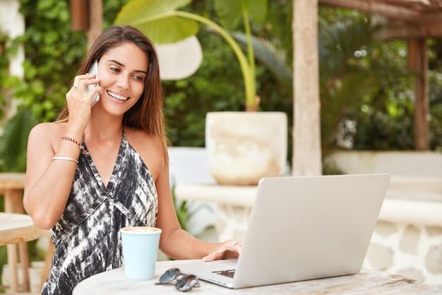 Открытый снимок красивой брюнетки с веселым выражением лица, которая разговаривает с другом по телефону, проверяет электронную почту онлайн на портативном компьютере