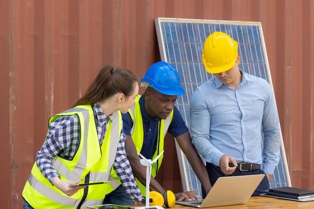 黒人のアフリカ人エンジニアの屋外ショットは、ヘルメット、保護眼鏡、安全装置を身に着けている電気ソーラーパネルを検査します。
