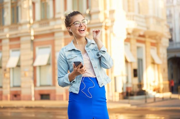 メガネの金髪の若い女性の屋外撮影は、デニムジャケットと青いスカートにさりげなく服を着て街を歩く