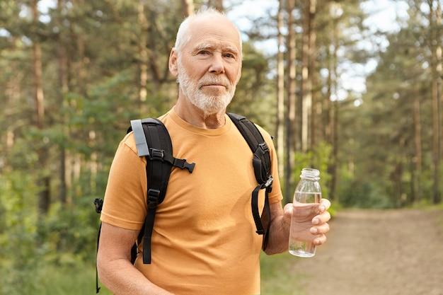 Снимок на улице уверенного в себе небритого пенсионера с лысой головой, держащего бутылку питьевой воды, который освежается в солнечный летний день, путешествуя в одиночестве с рюкзаком на природе