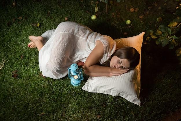 夜に庭で寝ているかわいい女性の屋外ショット