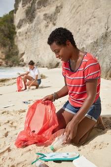 暗い肌の女の子の屋外ショットは、プラスチック容器を拾い、汚れたビーチでポーズをとる