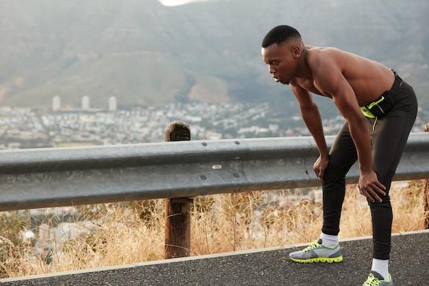 浅黒い肌の男の屋外ショットは、膝に寄りかかって、レース競技の後に息切れがあり、スニーカーを履いて、素晴らしい持久力を持ち、岩山の上に立っています。スポーツとトレーニングの概念