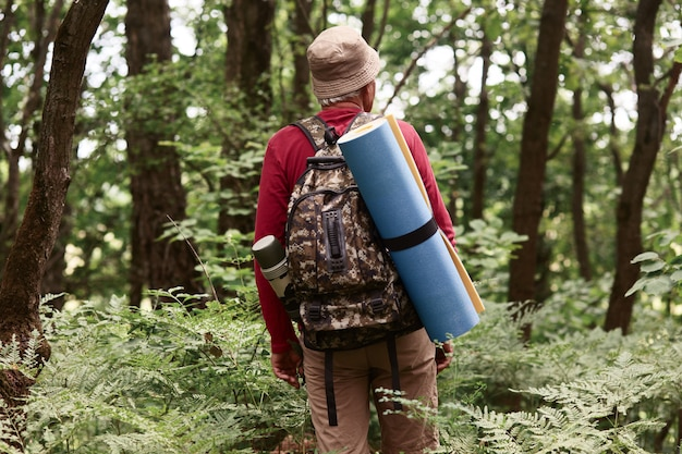 Открытый выстрел пожилого человека едет на вершину горы, старик турист в горах несет рюкзак и коврик