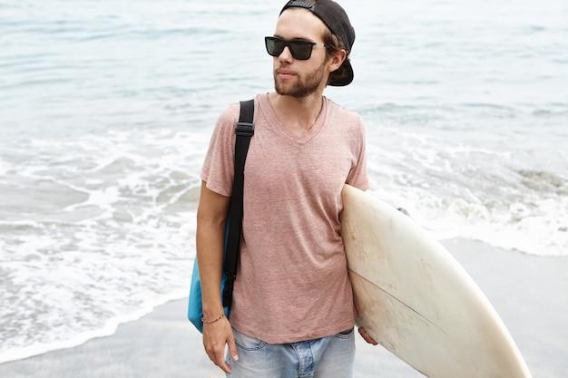 黒の色合いと彼の腕の下に白いサーフボードを運ぶスナップバックを身に着けているファッショナブルな若い男性モデルの屋外撮影