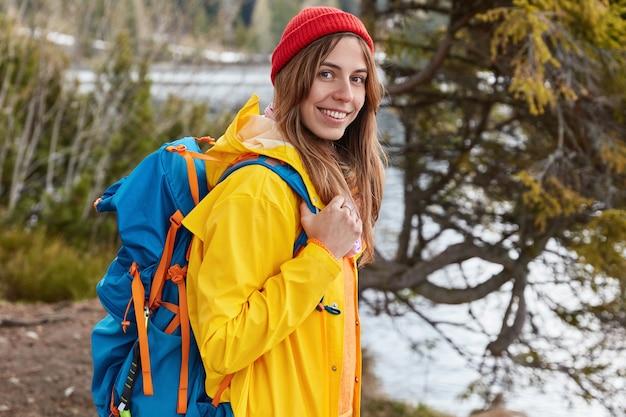 Открытый снимок радостной женщины с широкой улыбкой, стоящей боком перед камерой и несущей рюкзак