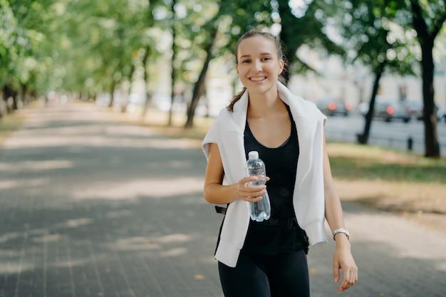 기쁜 스포티 한 여자의 야외 샷 병에서 신선한 물을 마신다 여름 동안 산책 녹색 도시 공원은 얼굴에 이빨 미소가 건강한 라이프 스타일을 리드. 훈련 후 아쿠아 발라 나스 복원