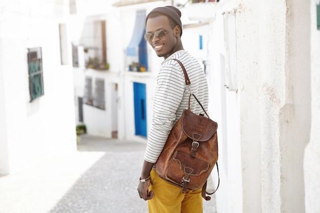 Открытый выстрел красивый счастливый молодой афро-американский мужчина путешественник с кожаным рюкзаком, стоя у бетонной стены на узкой улице во время осмотра достопримечательностей в курортном городе во время его летних каникул