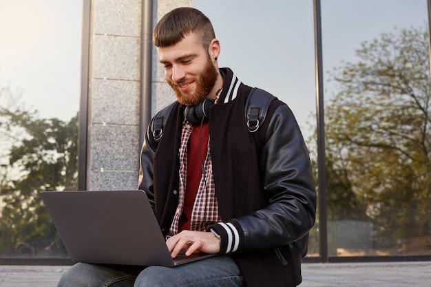 Открытый снимок красивого рыжебородого молодого парня, сидящего на улице, кладя ноутбук на колени, улыбающегося и болтающего со своими друзьями.