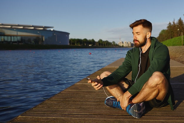 Снимок на открытом воздухе: красивый небритый молодой парень со щетиной проводит мирное летнее утро в одиночестве у озера, сидит с закрытыми глазами и слушает медитативные музыкальные треки на современном смартфоне