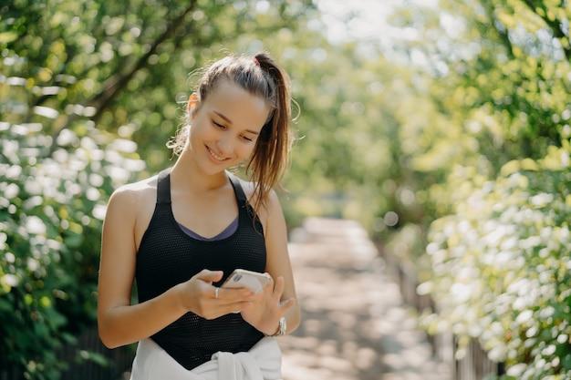 幸せな運動の若い女性の屋外ショットは、スマートフォンのスポーツ トラッカー アプリケーションを使用します。