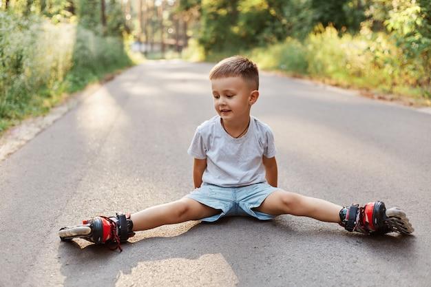 롤러 스케이트에 아스팔트 도로에 꼬기에 앉아 행복 한 어린 소년의 야외 샷, 옆으로 웃 고, 여름 공원에서 롤러 스케이트 학습을 찾고.