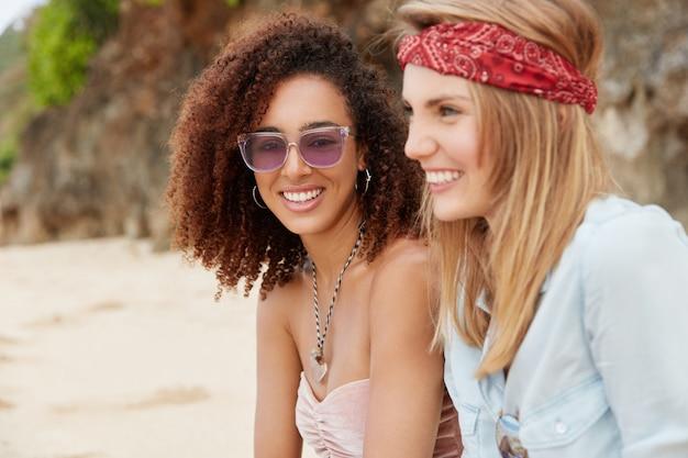 Снимок на открытом воздухе: счастливая смешанная лесбийская пара веселится вместе на пляже в тропической стране, в хорошем настроении, долгих и незабываемых летних каникулах, позитивно смотрит вдаль