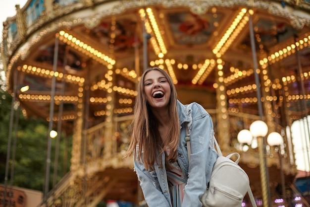 Открытый снимок счастливой молодой красивой женщины в джинсовом пальто и белом рюкзаке, стоящей над каруселью в парке развлечений и весело улыбаясь