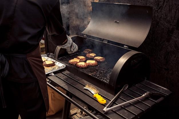 그릴에 치즈 버거 고기를 요리하는 남자의 야외 촬영