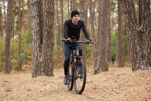 Открытый снимок человека езда на велосипеде в лесу вокруг деревьев, красивый мужчина в черной спортивной одежде и кепке