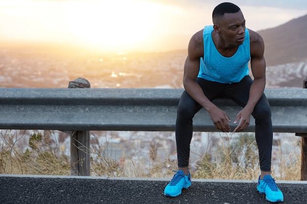 피트니스 몸을 가진 남자의 야외 촬영, 건강 관리, 신중하게 외모, 운동 후 휴식, 광고 콘텐츠 또는 홍보 텍스트 복사 공간이있는 일출 감탄