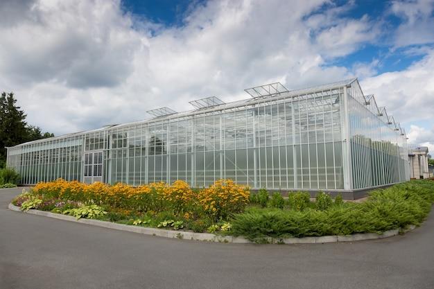 Открытый снимок современной стеклянной теплицы для выращивания овощей