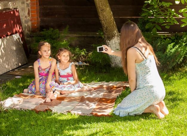 Открытый снимок матери, фотографирующей двух дочерей