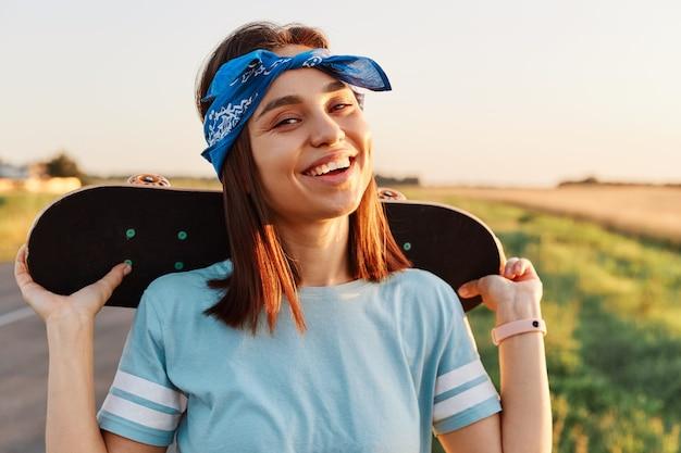 夏にスケートボードを楽しんで、肩にスケートボードを持って、歯を見せる笑顔でカメラを直接見ている黒髪の満足している楽しい女性の屋外ショット。