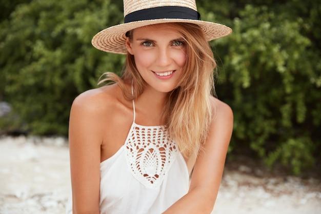 Снимок на открытом воздухе довольной молодой блондинки с привлекательной внешностью, одетой в летнюю одежду, радуется отдыху на пляже, позирует на фоне зеленой растительности, наслаждается жаркой солнечной погодой
