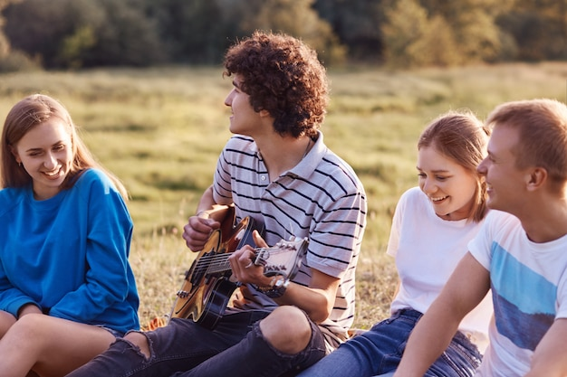 Открытый снимок довольных веселых друзей или компаньонов, которые в хорошем настроении, поют песни из детства, вспоминают позитивные моменты в дружбе, проводят свободное время на лугу на улице