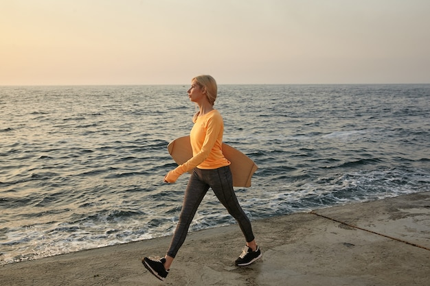 오렌지 긴 소매 상단과 어두운 레깅스를 입고 손에 균형 보드와 함께 이른 아침에 바닷가를 따라 걷는 예쁜 젊은 여성의 야외 촬영