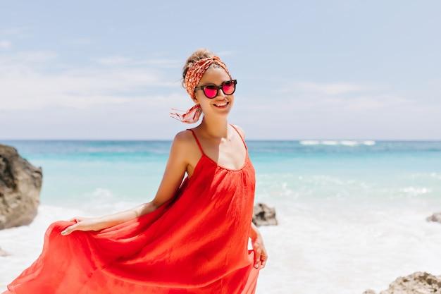 ビーチで喜んでポーズをとる洗練された日焼けした女の子の屋外ショット。赤いドレスで遊んで、ビーチで笑顔のゴージャスな若い女性の肖像画。