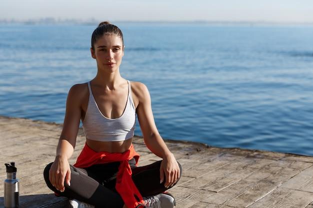 Открытый снимок расслабленной молодой женщины, медитирующей у моря, практикующей йогу